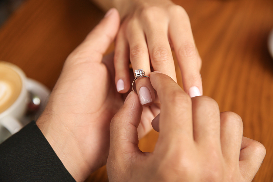 Man putting an engagement ring made in Brisbane to his girlfriend's hand